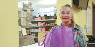 A woman at the Northeast NORC pantry holds a bag of food.