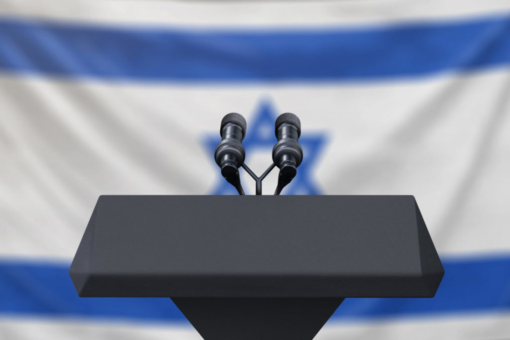 Podium lectern with two microphones and Israel flag in background