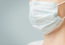 Unrecognizable woman in medical protective mask against virus and infection diseases, close-up. Copy-space in left part of image.