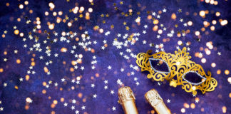Two champagne bottles, golden carnival mask and confetti stars on purple-blue backround. Flat lay of Christmas, New Year, Purim, Carnival celebration concept.