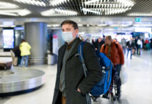 a man wearing a medical mask in an airport