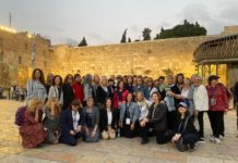 group shot of women standing in front of the western wall in Israel