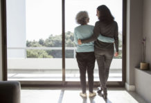 Rear view of happy mother and daughter standing embracing at window. Senior and mid adult women hugging and talking at home. Family relationships concept