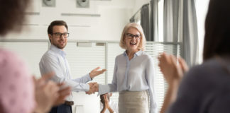 Happy manager boss praising old employee for good work get team appreciation acknowledgement handshaking successful worker congratulating promoting rewarding welcoming new partner, respect handshake