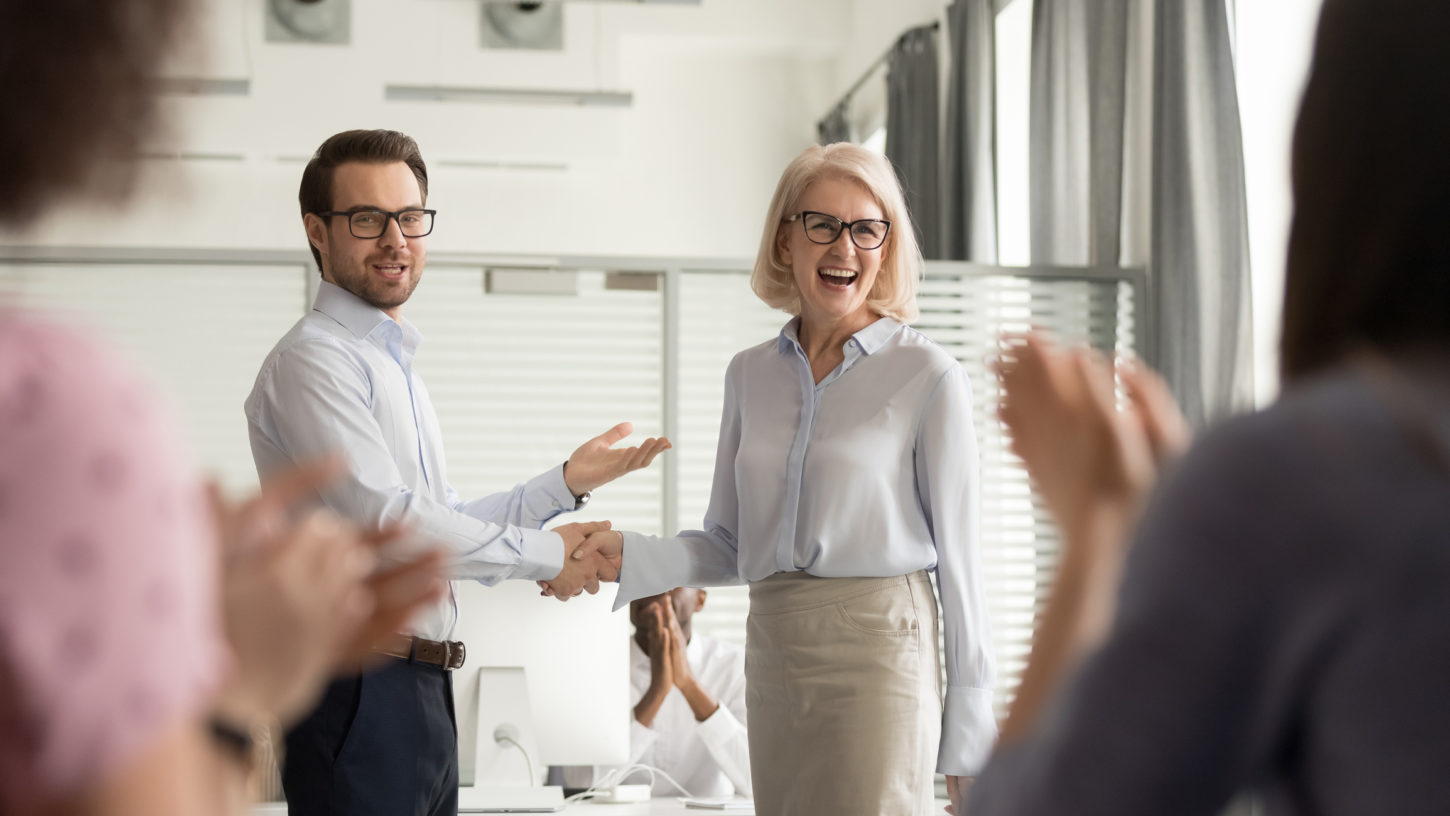 Happy manager boss praising old employee for good work get team appreciation acknowledgement handshaking successful worker congratulating promoting rewarding welcoming new partner, respect handshake