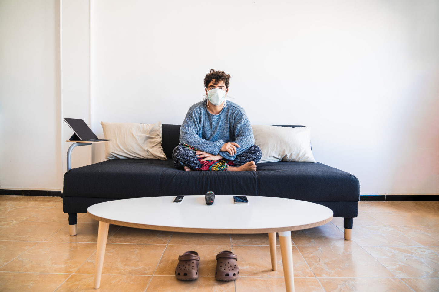 Young hispanic man sits on the couch while protecting against COVID-19 coronavirus due to it's virulency and impact on media and society