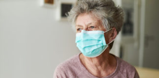 A senior citizen sits alone on her bed with a respirator or surgical mask and looks sadly and frightened out of the window and into the camera