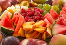 A mixture of their fruit. Peach, grapes, apple, watermelon, melon, raspberry, plum. Juicy and ripe pieces of fruit close-up.