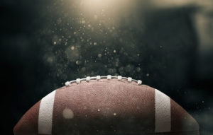 American football ball on black background illuminated