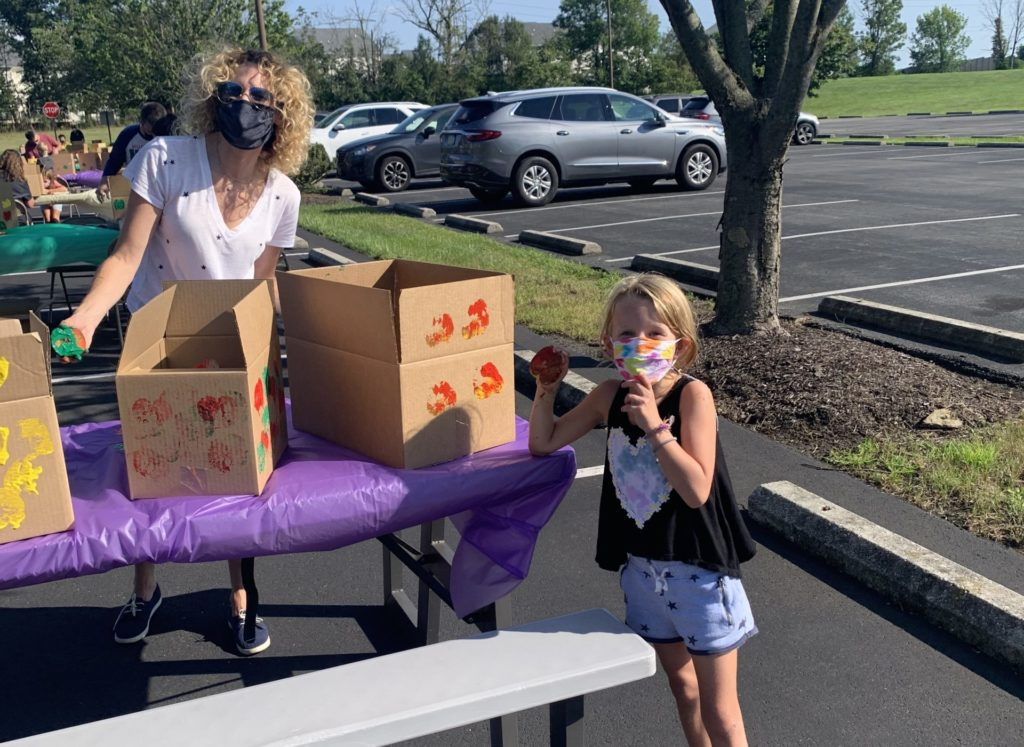 woman and child in masks outdoors at table with boxes