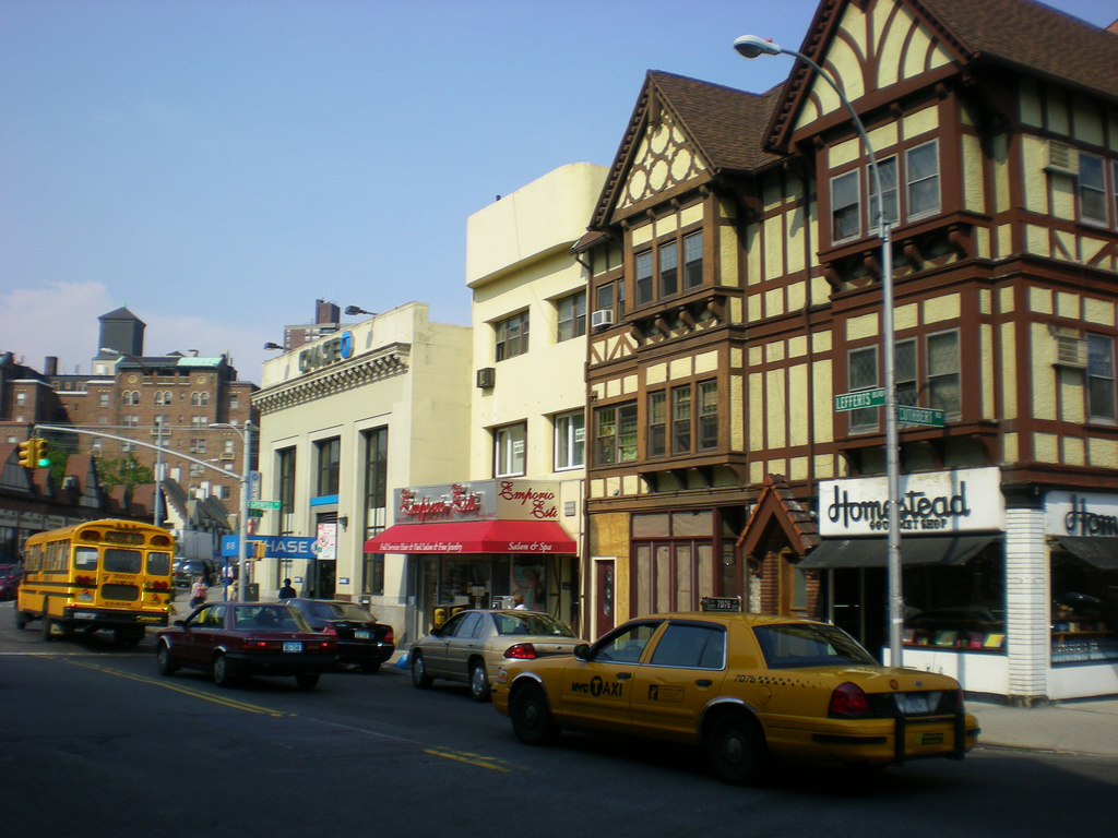 a street with businesses and taxis in Queens