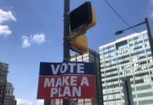 sign hanging on light pole that says vote make a plan