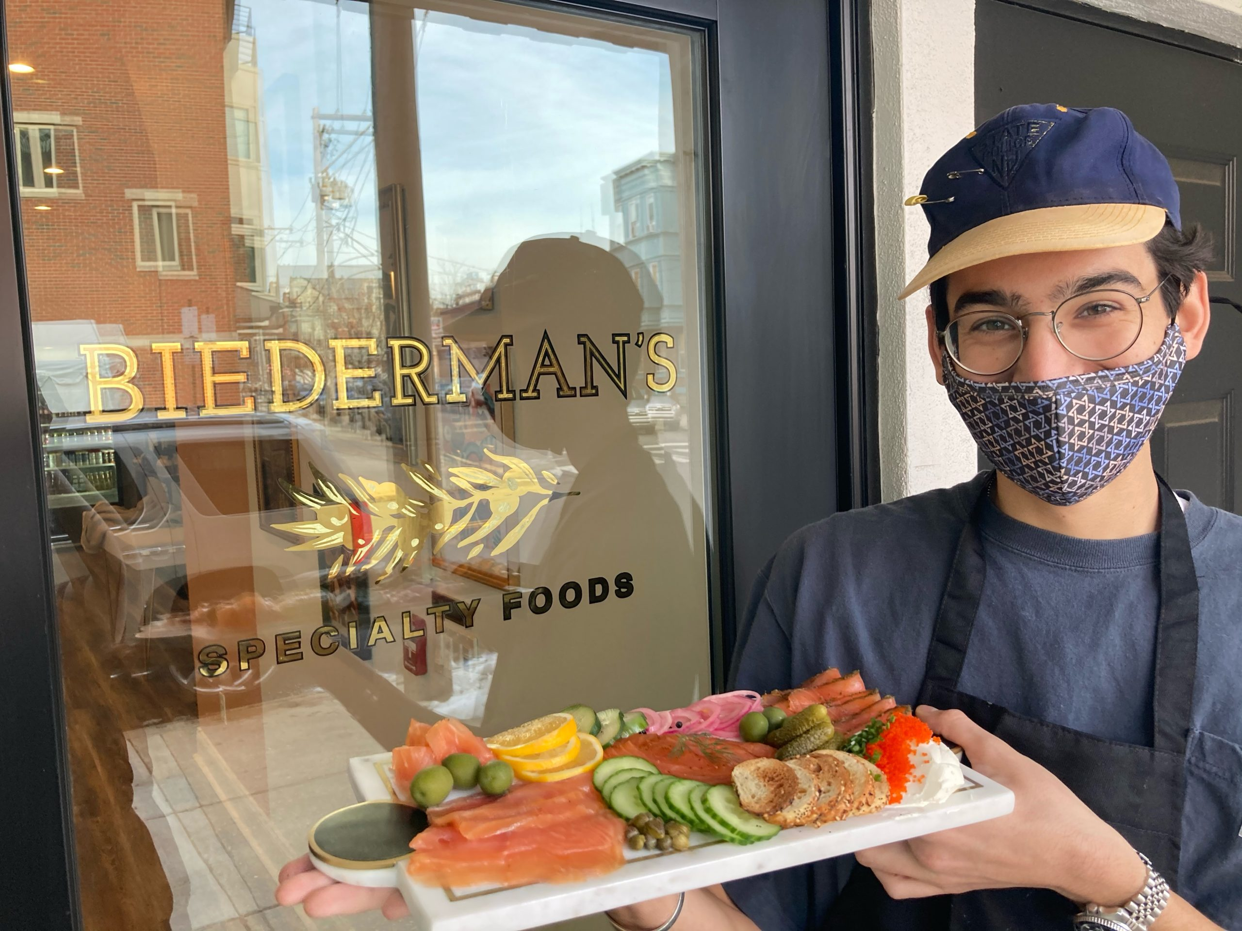 young man in mask holds plate of food in front of storefront