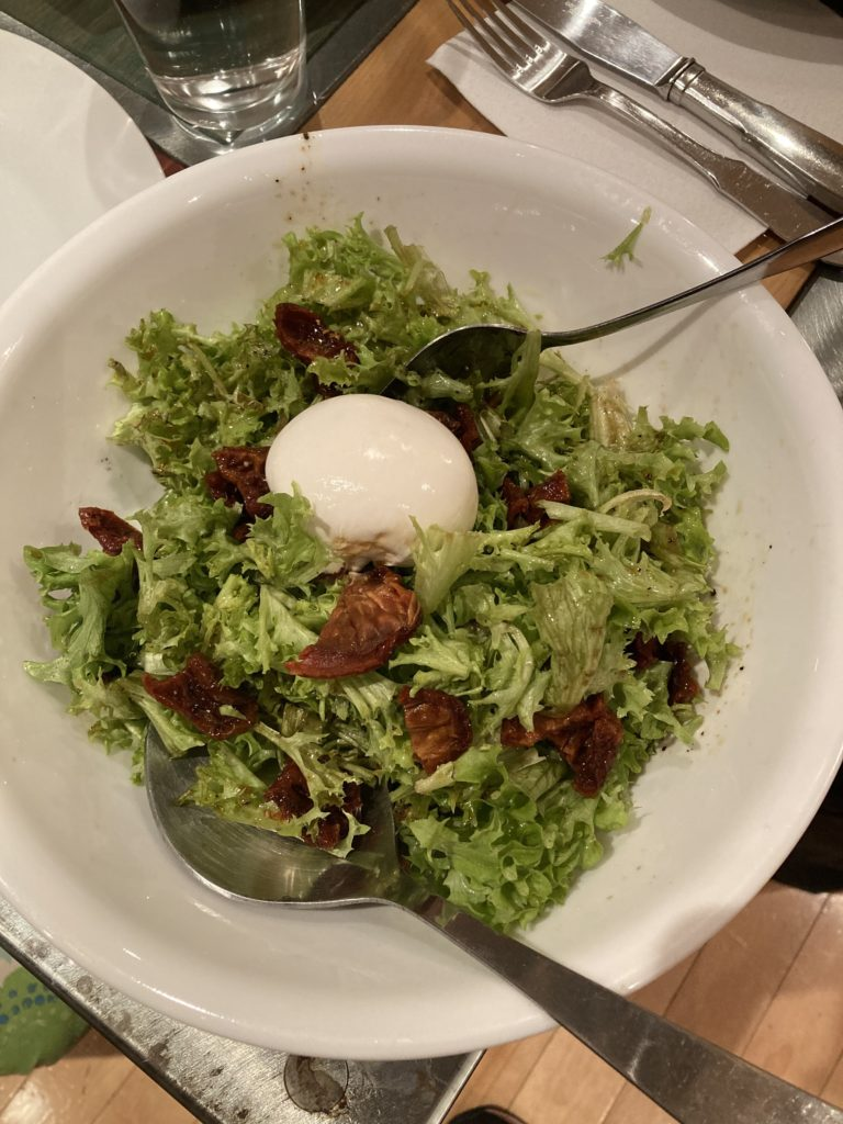 white bowl with greens and a single egg