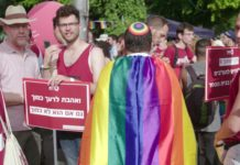 image of man in yarmulke wearing a rainbow flag with other people holding signs in hebrew