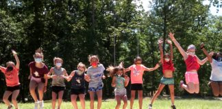 About 10 children wearing shorts and t-shirts jumping in the air outdoors