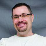 Author's headshot, wearing white shirt