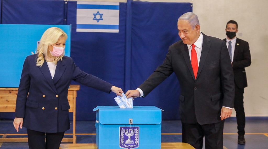 Benjamin and Sara Netanyahu drop their ballots into a ballot box