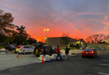 Sunset over a parking lot with two cars and people walking by