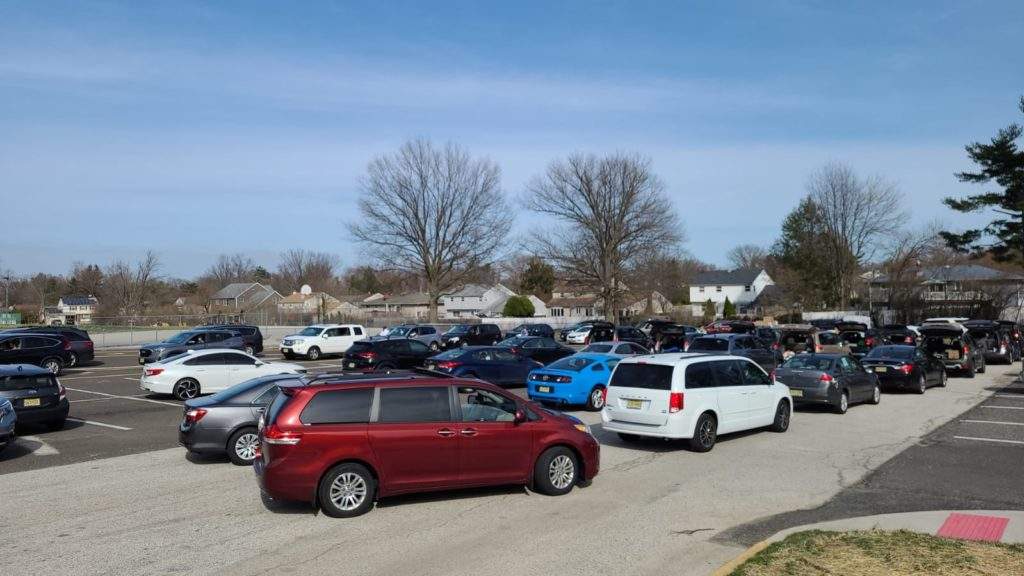 Many cars lined up in a parking lot