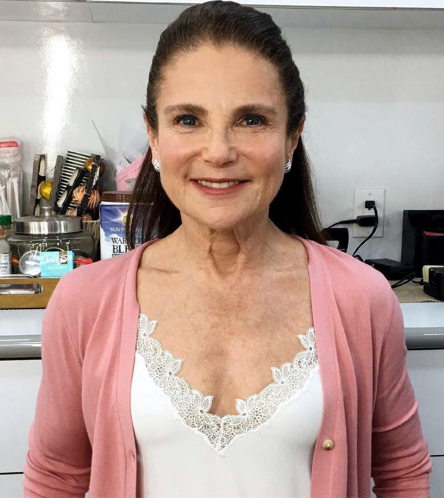 Headshot of Tovah Feldshuh wearing white shirt and pink sweater